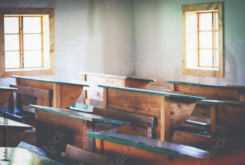 Old classroom with retro wooden desks vintage filter