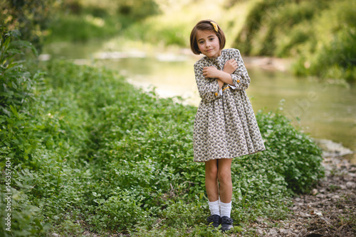Little girl in nature stream wearing beautiful dress Poster