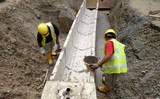 Construction workers installing precast u-shape concrete drain at the construction site. The drain was fabricated at factory and mobilized to site.  - 145361027
