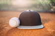 Baseball cap and ball on pitcher's mound