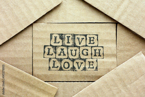 Cardboard card with words Live Laugh Love made by black alphabet stamps with piece of cardboard Poster