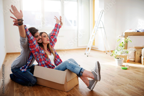 Happy young couple just moved new home unpacking boxes, having fun Poster