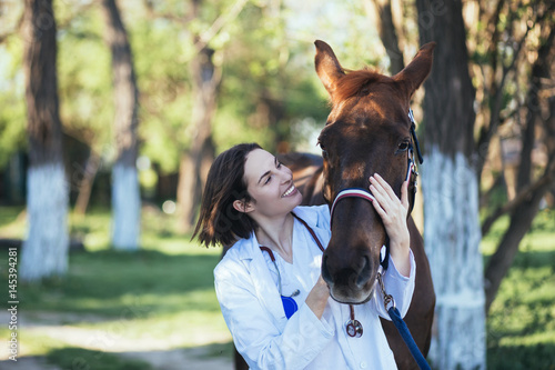 Vet petting a horse outdoors at ranch.
