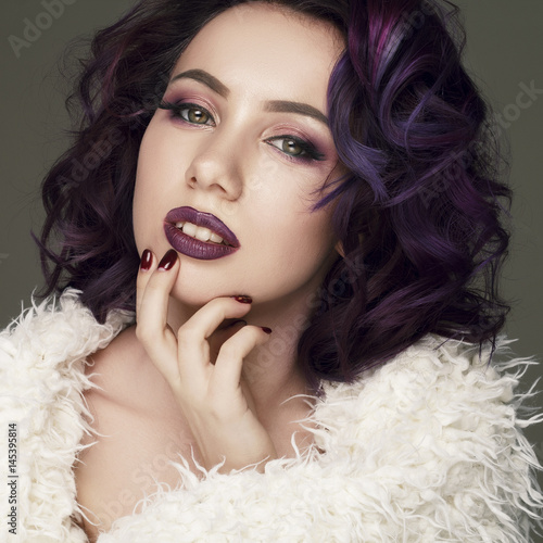 Portrait of young beautiful woman with violet make up and purple hair. Beauty concept.