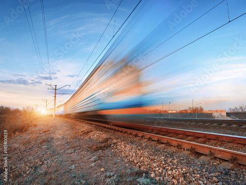 Wysoki prędkość pociąg w ruchu na torze szynowym przy zmierzchem. Zatarcie pociągu podmiejskiego. Stacja kolejowa przeciw kolorowemu niebieskiemu niebu. Podróże koleją, turystyka kolejowa. Wiejski przemysłowy krajobraz w zmierzchu