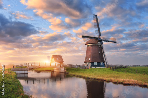 Plagát Windmill near the water canal at sunrise in Netherlands