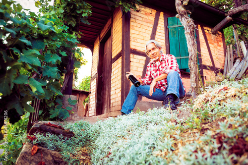 Keuken foto achterwand Crimson Winemaker Sitting By His Cottage