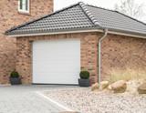 Gemauerte Garage mit einem weißen Tor - 145408048