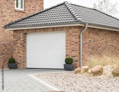 Fototapeta Gemauerte Garage mit einem weißen Tor