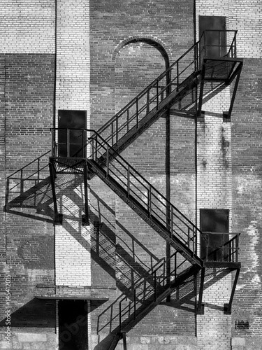 Steel stair and black doors on old industrial building brick wall. On direct hot sun. - 145412015