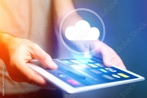 Concept of cloud storage icon flying out a tablet - technology concept