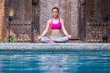 Asia woman doing yoga beside swimming pool