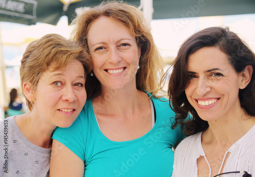 Portrait of three smiling 40 years old women outdoors Poster