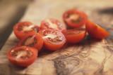 cherry tomatoea halves on olive cutting board, shallow focus