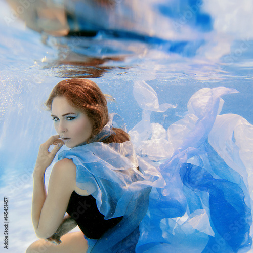 Plakat Underwater fashion portrait of beautiful young woman in blue dress