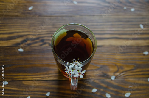 Black tea in a cup and cherry flowers on right side of tea cup. Top view. Selective focus