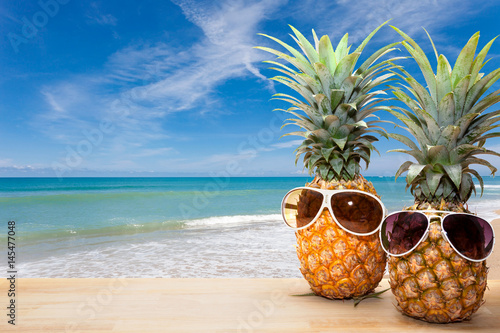 Poster pineapple with sunglasses on wood,concept summer background.