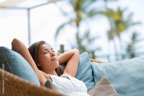 Leinwanddruck Bild Home lifestyle woman relaxing sleeping on sofa on outdoor patio living room. Happy lady lying down on comfortable pillows taking a nap for wellness and health. Tropical vacation.