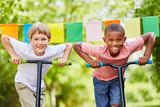 Zwei Kinder mit Roller sind ehrgeizig