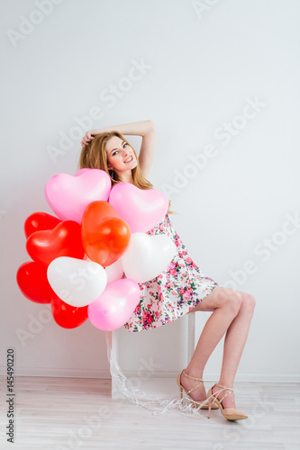 Poster Girl in romantic dress with balloons in the shape of a heart