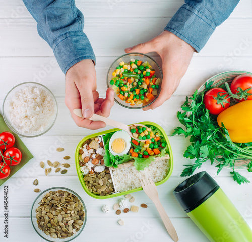 Top view of males hands filling lunch box on wooden background © lithiumphoto