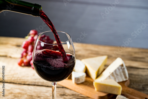 Pouring red wine into the glass against wooden table - 145495082