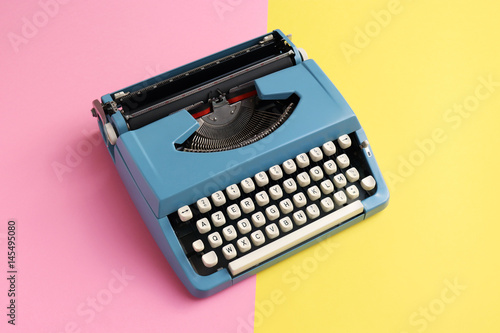 Vintage blue typewriter over a pastel background. Poster