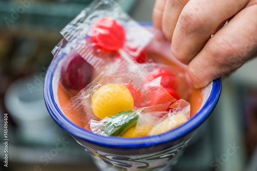 Hand holding a cup filled with plastic packaged lollipops Poster
