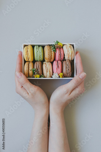 Foto op Canvas Macarons Hands holding gift box with delicious macaroons on the light blue background, top view