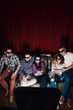 Group of young friends in 3d glasses have fun entertainment watching tv show on couch together, top view. Red curtain background with free space.