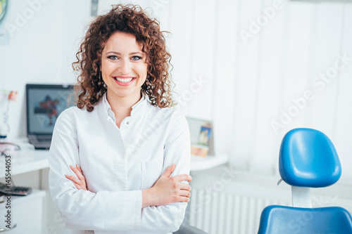 fototapeta na ścianę Portrait of female dentist. She standing at her office and she has beautiful smile.