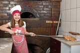 happy little girl cook real pizza in pizzeria