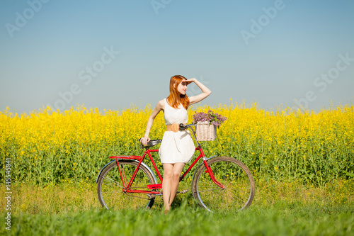 Plakat photo of beautiful young woman with bicycle on the wonderful flower field backgr
