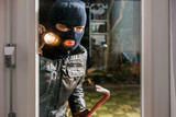 Masked burglar with flashlight and crowbar looking into glass window of house - 145548260