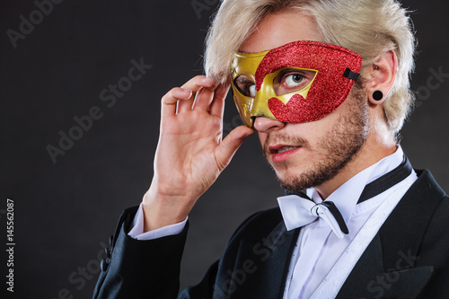 Poster Young man in carnival mask on dark