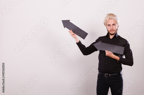 Man holding two arrows pointing same direction