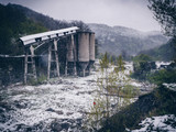 Post-industrial landscape of the abandoned mining facility in Anina, Romania in winter time (snowing)