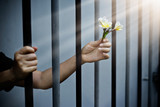 woman prisoner in prison with white flowers - 145585401