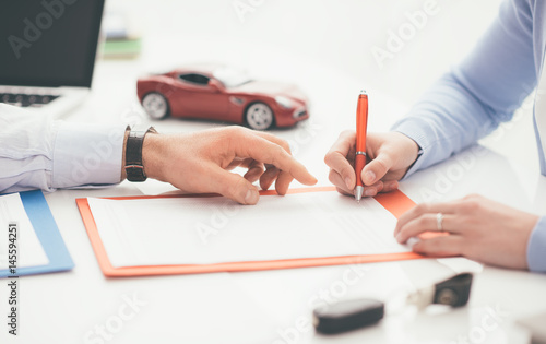 Driver signing a car insurance - 145594251