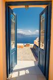 Opened door into summer concept. Oia village on  Santorini island, famous and popular Greek resort in Aegean sea. Europe. - 145594802