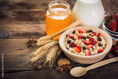 Oatmeal porridge with honey, strawberries and nuts