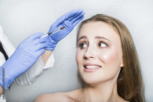Doctor aesthetician trying to make head beauty injections to female patient © pavelgulea