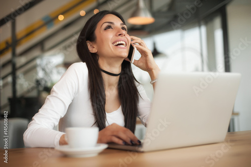 Happy woman having cell telephone conversation while sitting in cafe