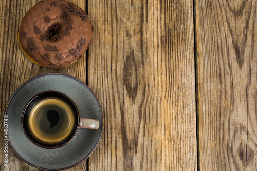 Poster One donut in chocolate glaze on wooden background
