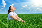 Business woman relaxing in green grass field outdoor under sun. Beautiful young girl dressed in suit resting, spring landscape, bright sunny day