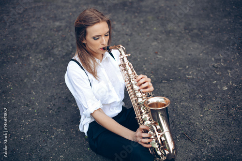 Plakát Playing young attractive girl in white shirt with a saxophone sitting sits on the earth - outdoor