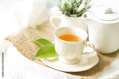 Zamyka w górę organicznie herbaty w białej filiżance z zielonym liściem, Herbacianej ceremonii czasu pojęcie