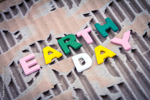 Poster Earth Day wording on abstract brown torn cardboard background