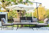 Cafe tables and chairs outside with big white umbrella and plant - 145671693