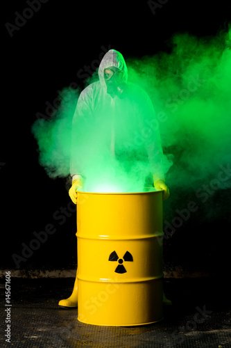 biohazard worker and radioactive green smoke coming out from yellow barrel